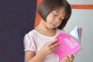 Asian Girl Reading Book - pediatric eye care Waterloo ON